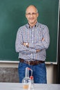 Teacher in chemistry class middle aged male standing with his arms folded against the blackboard with scientific glassware Stock Photography