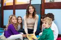 Teacher and children with book in classroom portrait of young sitting on floor Royalty Free Stock Photos