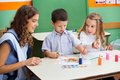 Teacher with children painting at desk little in classroom Stock Photos