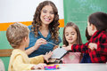 Teacher and children playing with xylophone in portrait of happy preschool classroom Royalty Free Stock Image