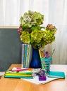 Teacher day hydrangea flowers and copybooks on the teacher s d desk glasses board pencils Stock Photos