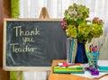 Teacher day hydrangea flowers and copybooks on the teacher s d desk glasses board pencils Stock Photo