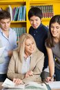 Teacher discussing with students at table in happy female college library Royalty Free Stock Photos