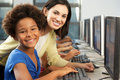 Teacher helping elelmentary students working at computers looking camera smiling Royalty Free Stock Photo