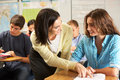 Teacher helping female pupil studying at desk in classroom looking each other talking Royalty Free Stock Photography