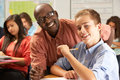Teacher helping male pupil studying at desk in classroom holding pen smiling camera Royalty Free Stock Photos
