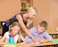 Teacher helping pupil explains how to solve the task