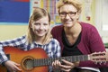 Teacher helping pupil to play guitar in music lesson class Stock Images