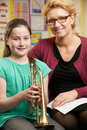 Teacher Helping Pupil To Play Trumpet In Music Lesson