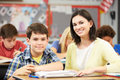 Teacher helping pupils studying at desks in classroom male student and looking and smiling the camera Royalty Free Stock Photos