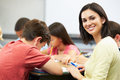 Teacher helping pupils studying at desks in classroom is turned around smiling to the camera Stock Image