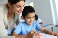 Teacher helping young boy writing