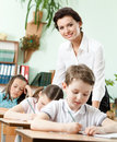 Teacher helps her pupils to do the task Stock Image