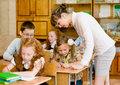 Teacher helps the schoolkids with schoolwork in classroom Royalty Free Stock Photo