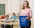 Teacher holding recycling bin Royalty Free Stock Images