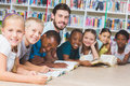 Teacher and kids lying on floor reading book in library Royalty Free Stock Photo