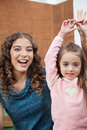 Teacher and little girl with hands raised portrait of cheerful young in classroom Royalty Free Stock Photo
