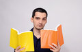 Teacher looking amazed at the books raising his eyebrow with suspicion surprised student man holding two orange and yellow blank Royalty Free Stock Photo
