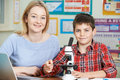 Teacher With Male Student Using Microscope In Science Class Royalty Free Stock Photo