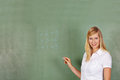 Teacher with math problem on writing a chalkboard in elementary school Stock Image