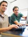 Teacher and mature student in computer room portrait of smiling showing something on screen to the Royalty Free Stock Images