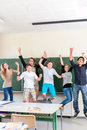 Teacher motivating students in school class successful and jump front of a blackboard with math work a classroom or while lesson Stock Photos