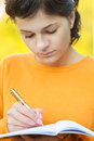 Teacher with pen and writing book beautiful young school in yellow sweater Royalty Free Stock Images