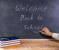 Teacher placing smile symbol on welcome back to school message w Royalty Free Stock Photo