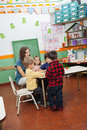Teacher playing with children in kindergarten young preschool Stock Photos