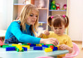 Teacher and preschooler play with building bricks Stock Photo