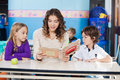 Teacher reading book while children listening to beautiful her in classroom Stock Photo