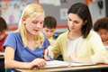 Teacher reading with female pupil in class Royalty Free Stock Image