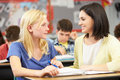 Teacher reading with female pupil in class looking at each other smiling Stock Photography