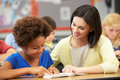 Teacher reading with female pupil in class smiling whilst points at the book Stock Photos