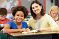 Teacher reading with female pupil in class and student looking smiling at camera Stock Photography