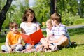 Teacher reads a book to children in a summer park and reading together the Royalty Free Stock Photos