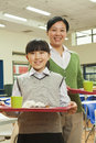 Teacher and school girl portrait in school cafeteria Stock Photos