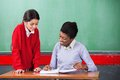Teacher and schoolgirl reading together at desk young african american female in classroom Royalty Free Stock Photo