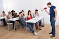 Teacher shouting through megaphone on university students angry in classroom Stock Photos