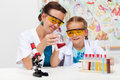 Teacher showing basic chemistry experiment to a little student in elementary school Royalty Free Stock Image