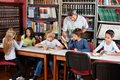 Teacher showing book to schoolboy in library happy mature male with students studying at table Stock Photography