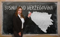 Teacher showing map of bosnia herzegovina successful beautiful and confident young woman on blackboard for presentation marketing Stock Images