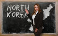 Teacher showing map of north korea on blackboard successful beautiful and confident young woman for presentation marketing Stock Photography