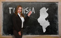 Teacher showing map of tunisia on blackboard successful beautiful and confident young woman for presentation marketing research Royalty Free Stock Photo