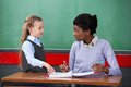 Teacher smiling while looking at schoolgirl young african american female in classroom Royalty Free Stock Photography