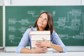 Teacher with stack of books looking up at classroom desk thoughtful mid adult female Stock Images