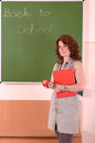 Teacher stand with book and apple in her hand classic board the background Royalty Free Stock Image