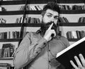 Teacher or student with beard studying in library. Scientist busy with exploring book. Man on busy face reading book Royalty Free Stock Photo