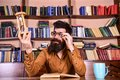 Teacher or student with beard studying in library. Scientist with eyeglasses sits at table and looks at hourglass. Man Royalty Free Stock Photo