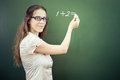 Teacher or student wrote on blackboard with chalk at classroom arithmetic digits one plus two and looking the camera girl dressed Stock Photo